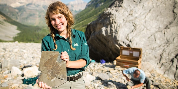 Staff showing a Burgess Shale fossil at the top of the mountains. Photo credit: Paul Zizka.