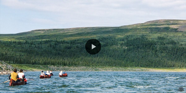 Several people in canoes on a river in the Northwest Territories.