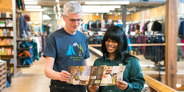 A Parks Canada employee provides information to a man in a MEC store.