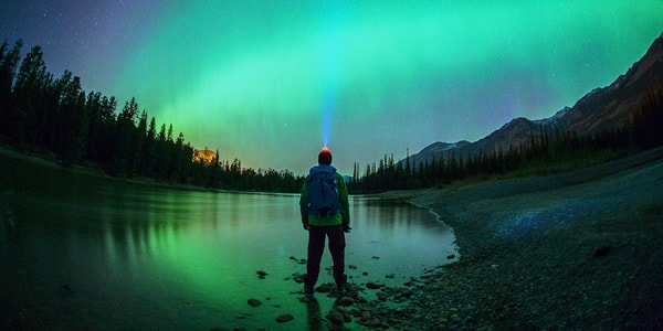 A man standing along a lake shoreline, looking at the northern lights in the glow of his headlamp.